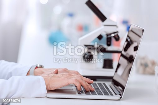 Cropped shot of scientist using laptop with blank screen in laboratory