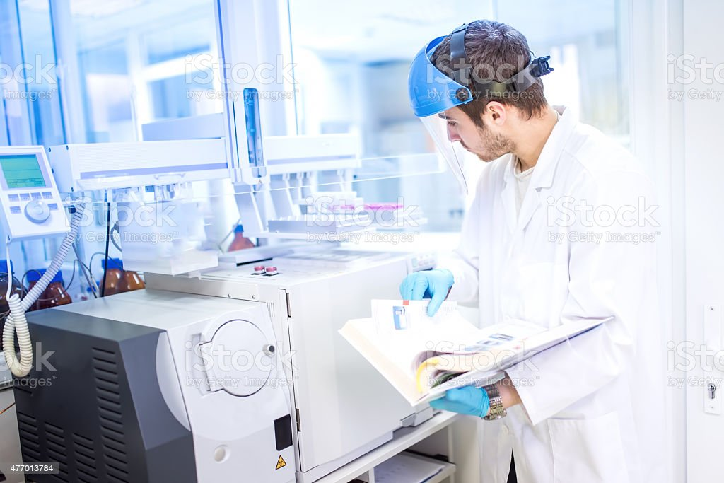 Scientist using manual for programming a chemical computer machinery stock photo