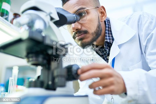 Portrait of young Middle-Eastern scientist looking in microscope while working on medical research in science laboratory, copy space