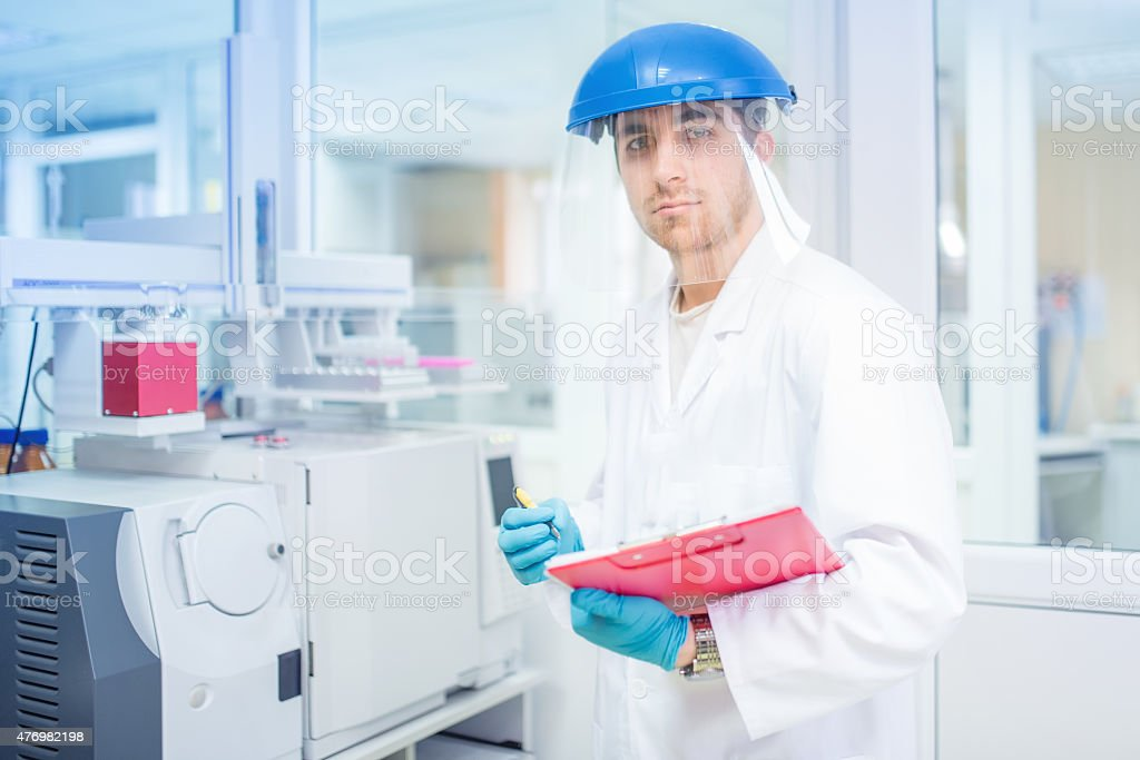 Scientist using protective rubber gloves and helmet, doing experiments stock photo