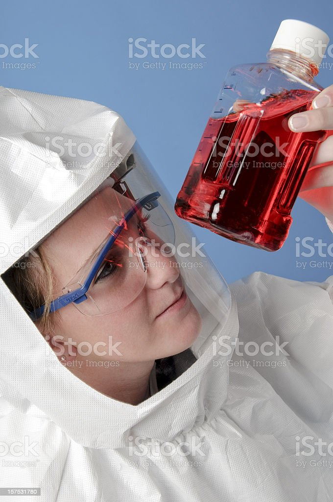 Scientist Wearing Protective Suit Looking at a Red Sample royalty-free stock photo
