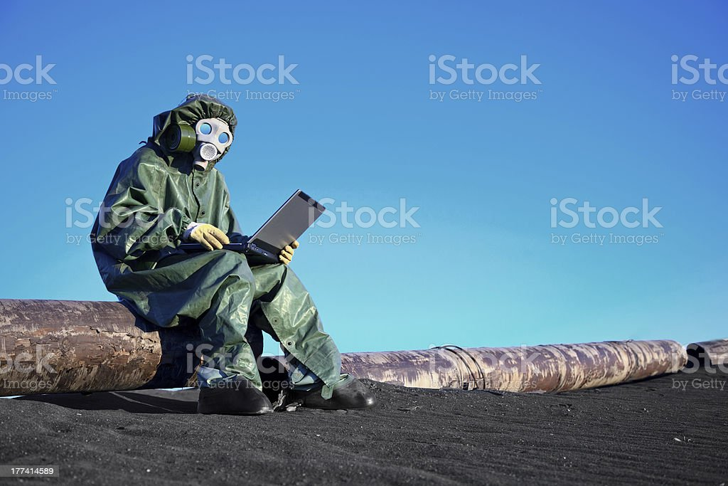 Scientist with a laptop on chemically contaminated area A scientist working with a laptop on a chemically contaminated area(unrecognizable person) Adult Stock Photo
