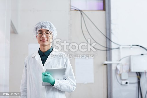 Portrait of Asian young man in white coat holding digital tablet smiling at camera while standing in the lab