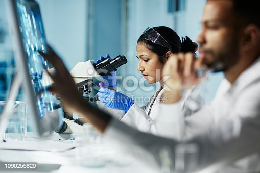 Scientist Working on Computer In  Modern Laboratory NOTE TO INSPECTOR: all graps, dna models, charts are made by me