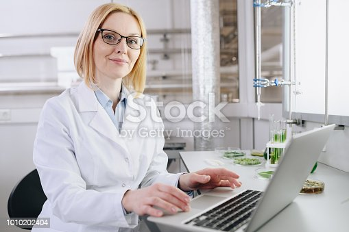 Portrait of blonde female scientist in eyeglasses sitting at desk and working with laptop during scientific experiment