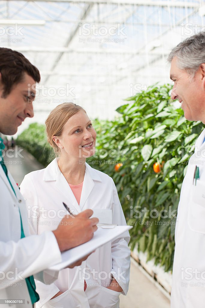 Scientist writing on clipboard outside greenhouses royalty-free stock photo