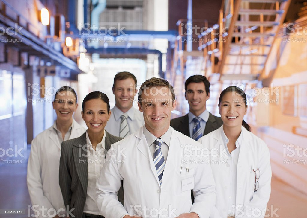 Scientists and business people standing together in factory stock photo