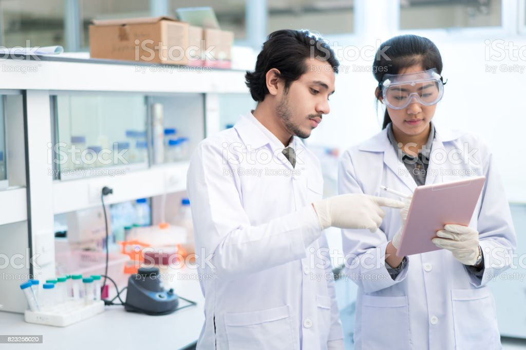 Scientists asian in the laboratory they use a tablet recording the results. stock photo