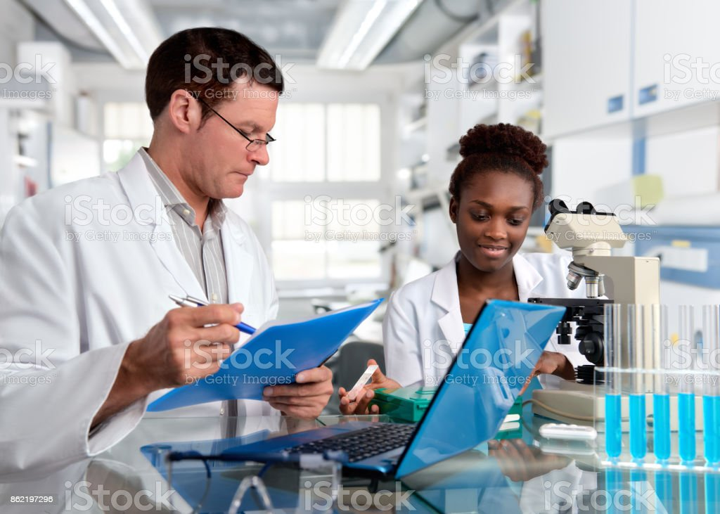Scientists, Caucasian male and African female, work in laboratory stock photo