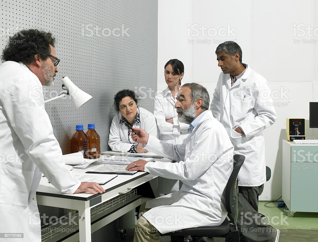 scientists discussing around table in lab royaltyfri bildbanksbilder