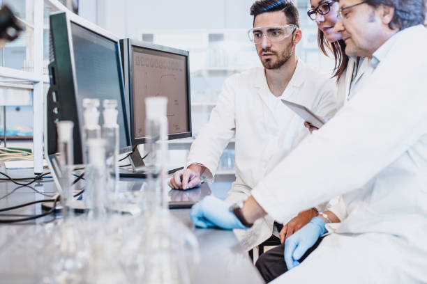 Scientists discussing in the laboratory, using computer stock photo