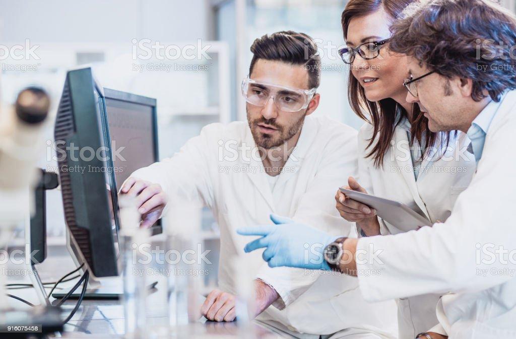 Wissenschaftler diskutieren im Labor, Computer verwenden – Foto