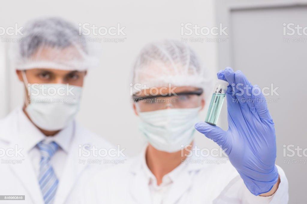 Scientists examining green precipitate in tube stock photo
