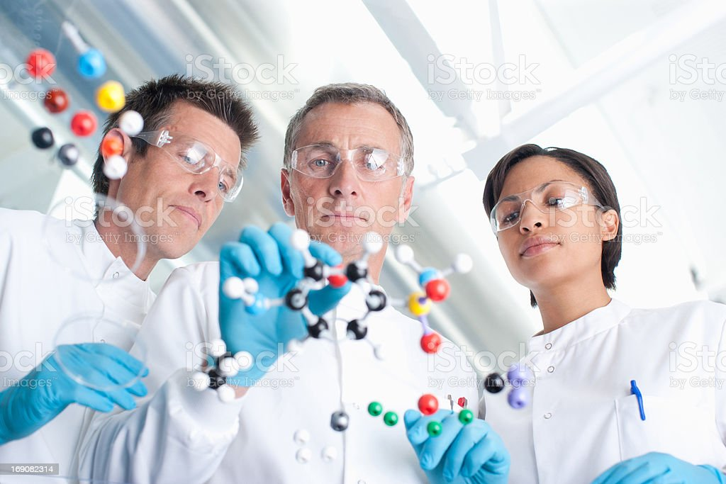 Scientists examining molecular models in lab stock photo