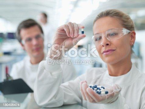 istock Scientists examining pills in lab 130405474
