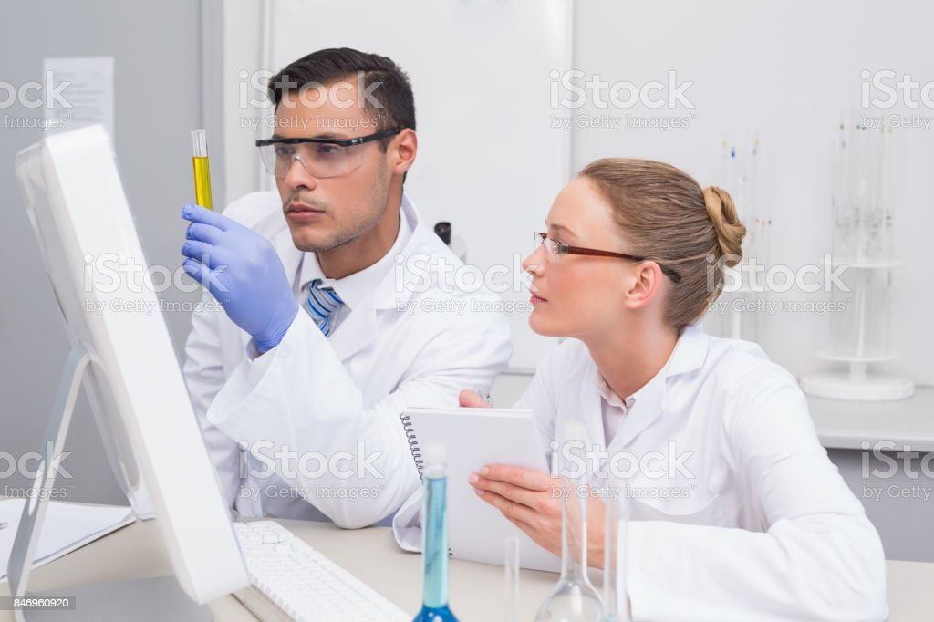 Scientists examining yellow precipitate in tube stock photo