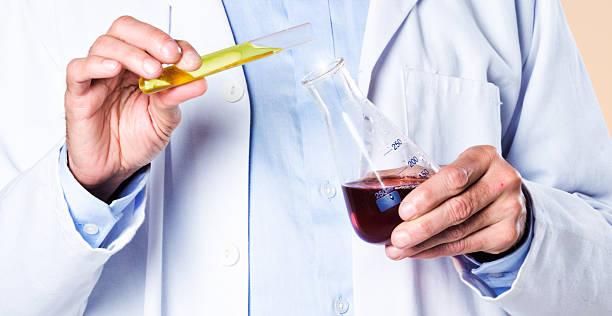 scientist's hands add yellow liquid to red fluid in flask - laboratory add flask bildbanksfoton och bilder