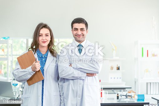 Scientists In Laboratory. Medical Workers At Work. Portrait Of Beautiful Young Woman And Hansome Happy Man In Modern Scientific Laboratory Working Together.
