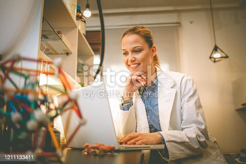 Scientists in the laboratory use a Laptop recording the results. Young medical student learning and writes in laborator. Portrait of confident female scientist working on laptop in chemical laboratory