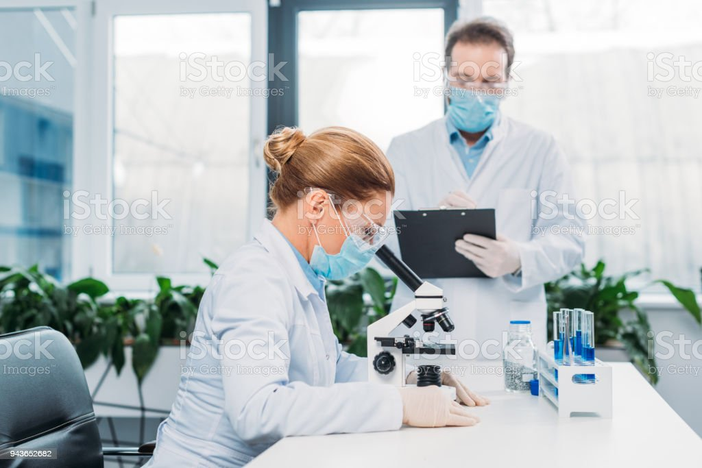 scientists in white coats and goggles working with reagents and microscope in laboratory stock photo