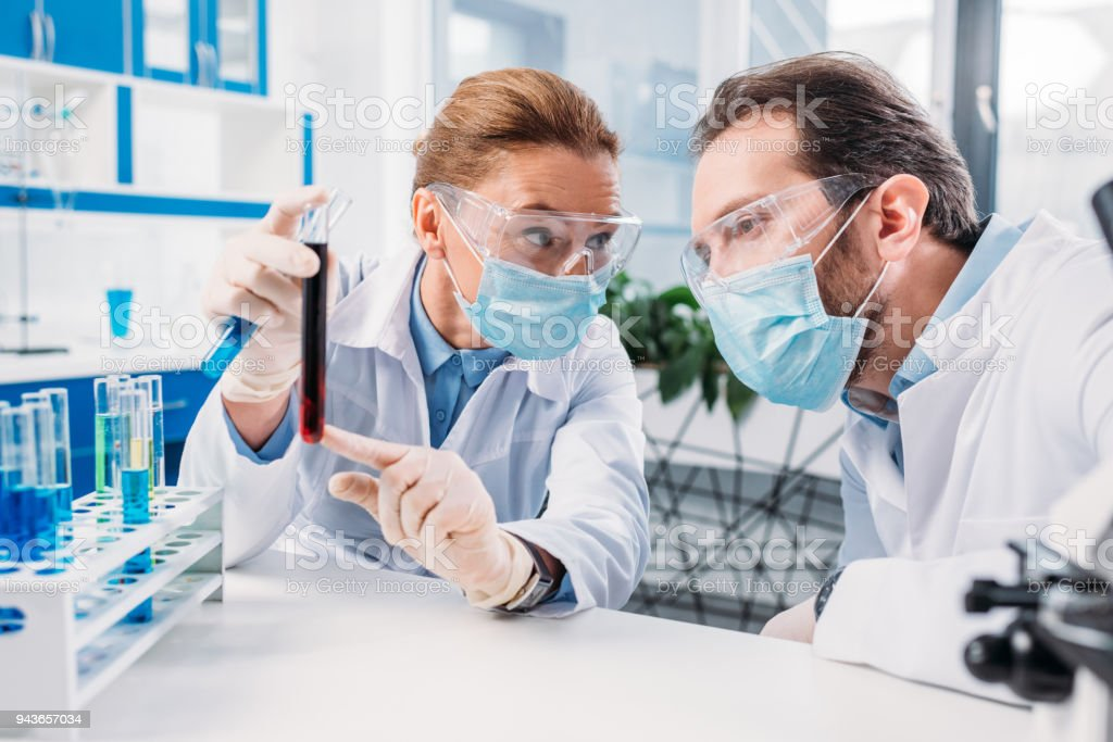 scientists in white coats and medical masks working with reagents in laboratory stock photo