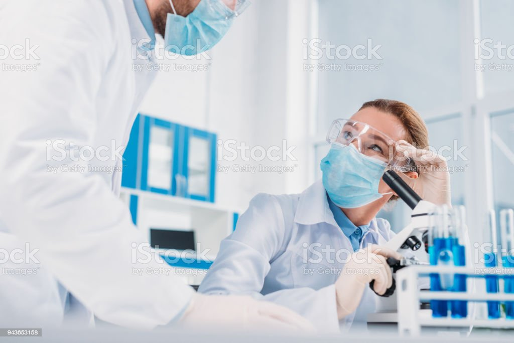 scientists in white coats, medical gloves and goggles making scientific research together in laboratory stock photo