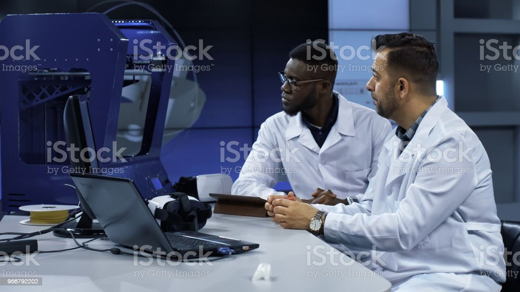 Scientists investigating 3-D printed model stock photo
