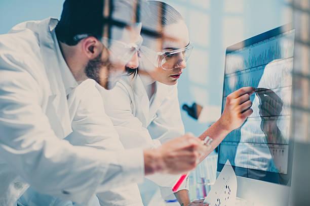 los científicos que en una secuencia de adn en el monitor - investigación genética fotografías e imágenes de stock