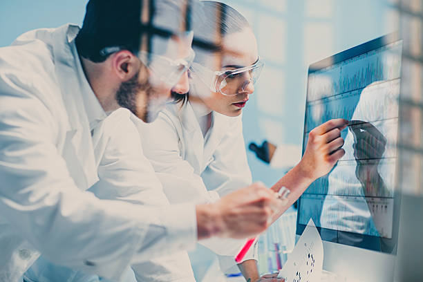 scientists looking at a dna sequence on the monitor - medical research stock photos and pictures