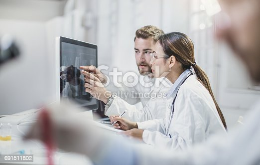 506251164istockphoto Scientists Looking at Computer Monitor and Discussing 691511802
