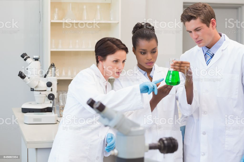 Scientists looking at green precipitate stock photo