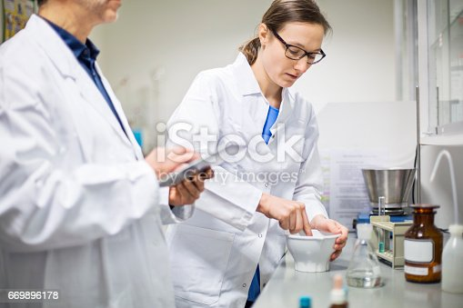 Male and female scientists making medicine at laboratory. Doctors are working together at pharmacy. They are wearing lab coats.