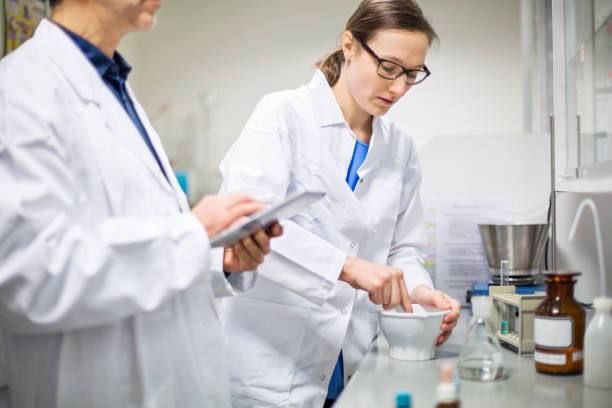 Scientists making medicine at pharmacy stock photo