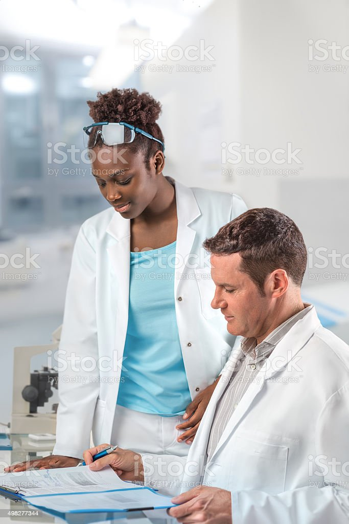 Scientists, male and female, work in research facility stock photo