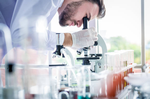 los científicos hombre trabajo y seguir el microscopio en el laboratorio - biotecnología fotografías e imágenes de stock