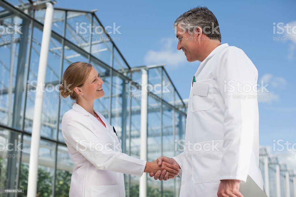 Scientists shaking hands outside greenhouses royalty-free stock photo
