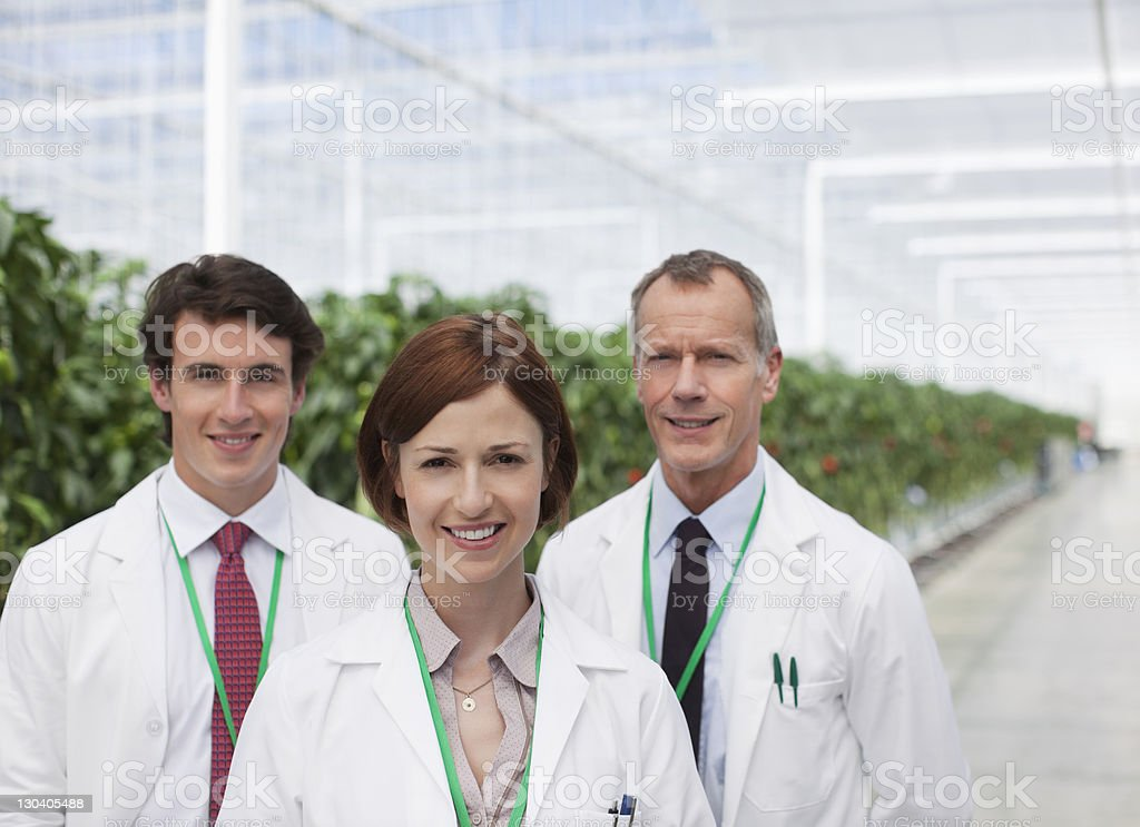 Scientists smiling in greenhouse royalty-free stock photo