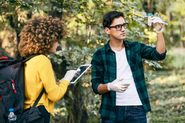 Scientists study water in the forest Men and women scientists are looking at a sample of polluted water in the forest. A scientific ecologist in the forest takes water samples. specimen holder stock pictures, royalty-free photos & images