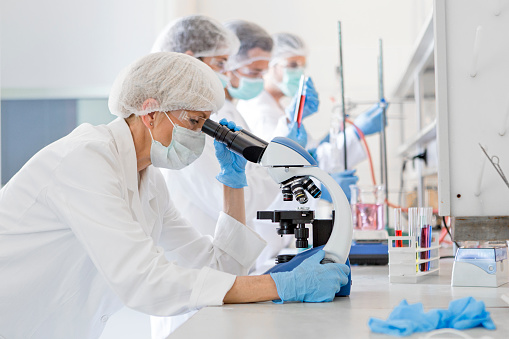 Scientists in protective suits in a science laboratory study a virus