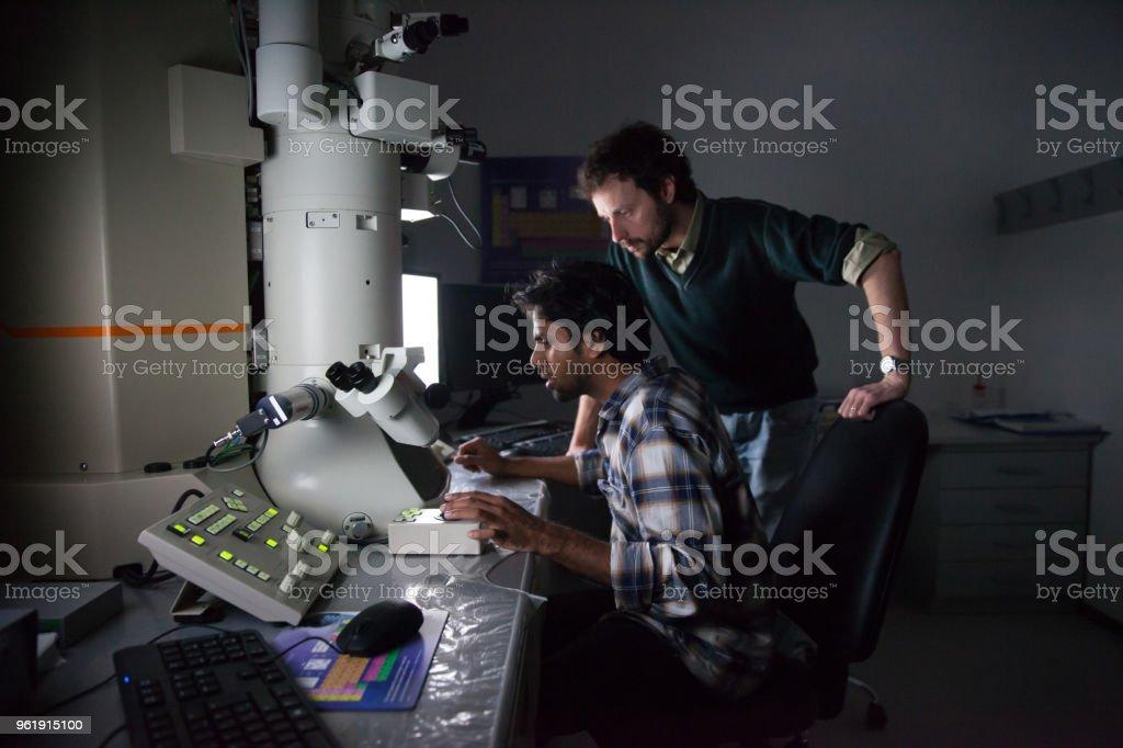 Científicos usando microscopio electrónico de emisión de campo - foto de stock