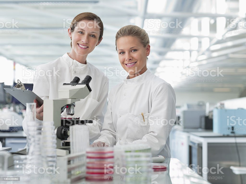 Scientists using microscope in lab royalty-free stock photo