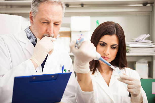 Scientists working in a laboratory Scientists at work in a laboratory als stock pictures, royalty-free photos & images