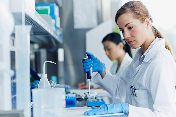 scientists working in modern laboratory - biotecnología fotografías e imágenes de stock