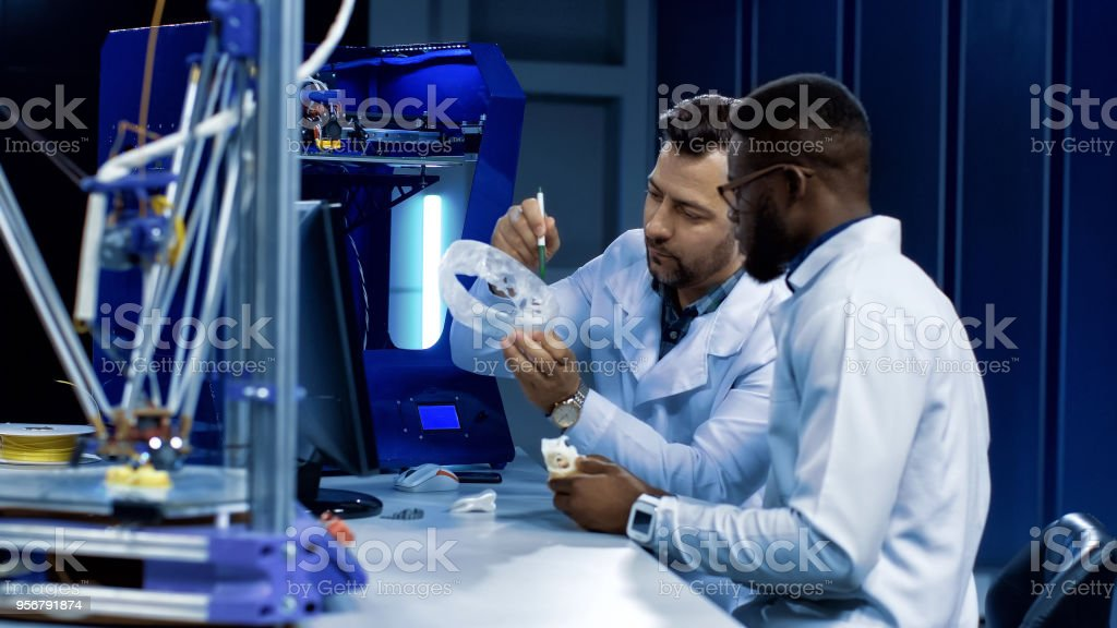 Scientists working on 3-D printing in medicine purposes stock photo
