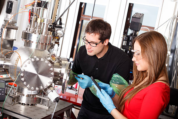 scientists working with laser deposition chamber - physics stock photos and pictures