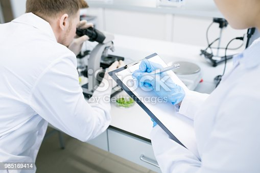 istock Scientists writing results of research under microscope 985169414