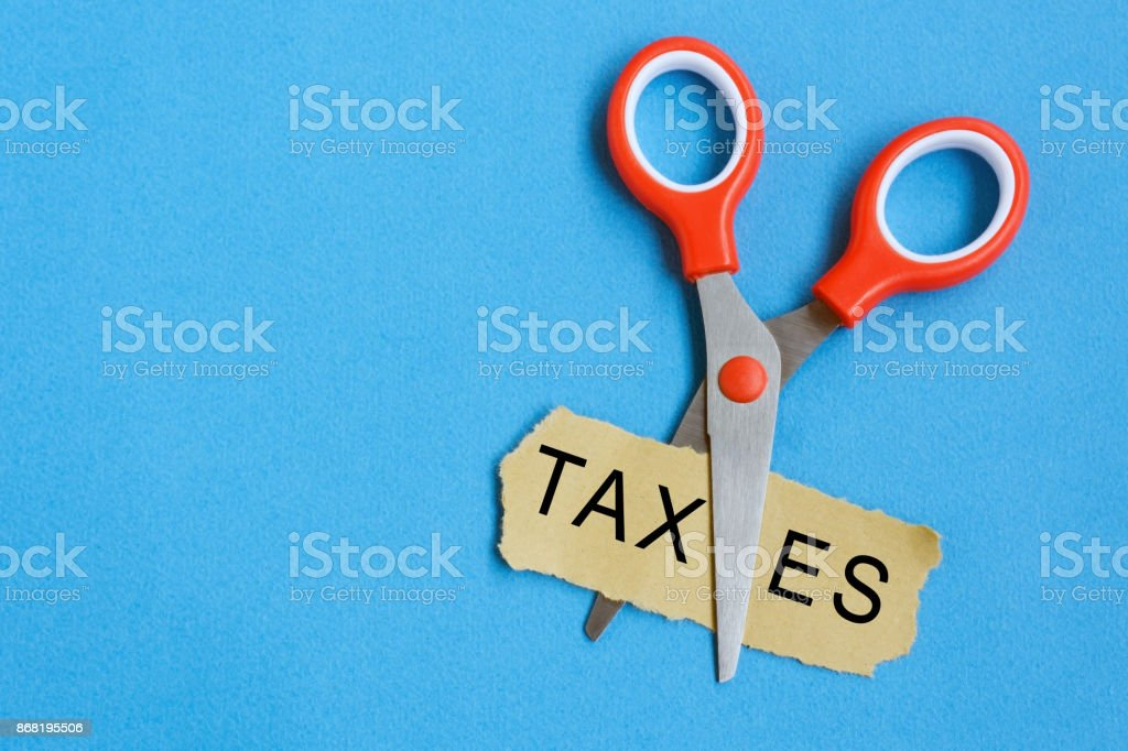 Scissor Cutting Taxes Word on Paper stock photo