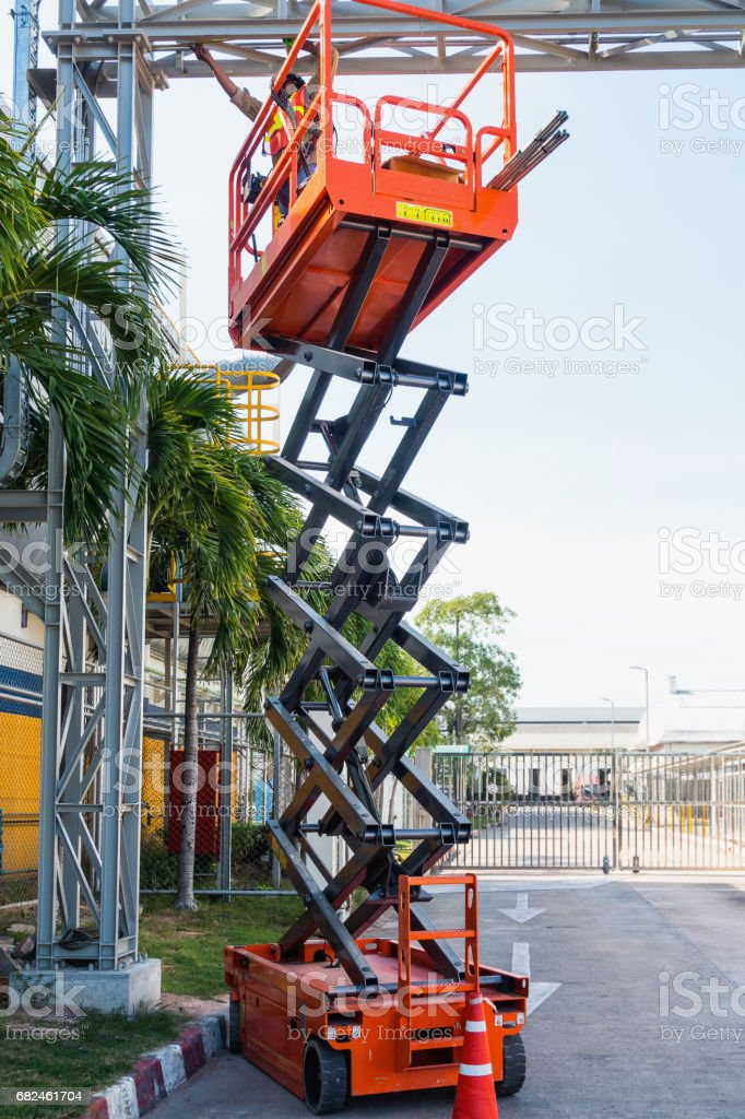 Scissor lift platform and electrical technician operated wiring. stock photo