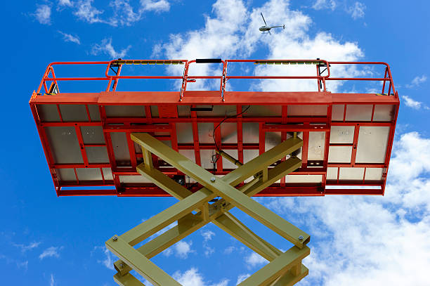 Scissor lift platform Scissor lift platform with hydraulic system at maximum height range painted in orange and beige colors, large construction machine, heavy industry, white clouds and blue sky on background  retrieving stock pictures, royalty-free photos & images