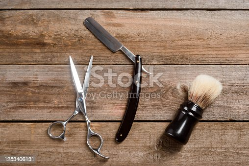 834518170 istock photo Scissors, a sharp straight razor and a brush on the wooden boards 1253406131